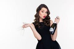 相当嬉戏的卷曲妇女提供的香槟和拿着两块玻璃 免版税库存图片