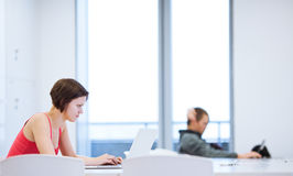 相当学习在图书馆里的年轻大学生 免版税库存照片