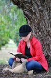 相当学习在巨大的结构树旁边的十几岁的女孩圣经在公园 库存照片