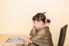相当学习的小女孩坐在桌后和,读书 库存图片