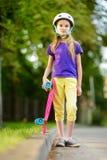 相当学会的小女孩踩滑板在美好的夏日在公园 享受踩滑板的乘驾的孩子户外 免版税图库摄影