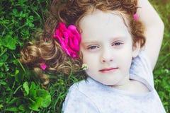 相当小女孩与在她的在绿草的头发起来了在summe 免版税库存图片