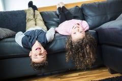 相当小女孩和男孩在他们的在沙发的后面说谎 免版税库存照片