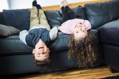 相当小女孩和男孩在他们的在沙发的后面说谎 免版税库存图片