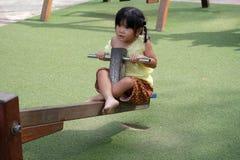 相当小女孩在泰国穿戴了在室外跷跷板在操场 免版税库存图片