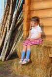 相当小女孩坐黄色干草在木房子附近墙壁  免版税库存图片