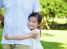 相当小女孩拥抱父亲腰部在公园 免版税库存照片