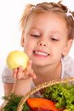 相当小女孩用苹果和蔬菜 免版税库存图片