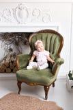 相当小女孩画象在家坐椅子在圣诞节的一个壁炉附近 免版税库存图片