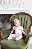 相当小女孩画象在家坐椅子在圣诞节的一个壁炉附近 免版税库存照片