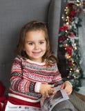相当小女孩画象在家与书坐在圣诞节的一把椅子 免版税库存照片