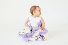 相当小女婴坐与被隔绝的格子花呢披肩的地板 免版税库存照片