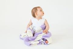 相当小女婴坐与被隔绝的格子花呢披肩的地板 免版税库存图片
