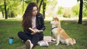 相当小姐是阅读书在公园,并且轻拍逗人喜爱的狗shiba inu品种,有教养的宠物坐 股票录像