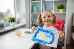 相当小孩与五颜六色的油漆的女孩绘画在家 免版税库存照片