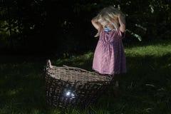 相当小白肤金发的儿童女孩在有篮子的森林 免版税库存照片
