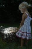 相当小白肤金发的儿童女孩在有篮子的森林 库存图片