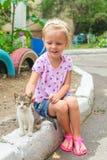 相当小美丽的女孩使用与无家可归者 免版税图库摄影