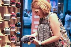 相当少妇发现她喜爱的鞋子 免版税库存照片