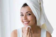 相当少妇在卫生间里时清洗她的面孔,当看在镜子 免版税库存照片