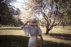 相当少妇在夏天庭院里,与帽子的偶然浪漫样式 免版税库存照片