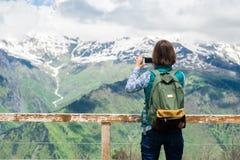 相当少妇在山上面的女孩逗留和与巧妙的电话的采取图片在美好的背景 五颜六色 图库摄影