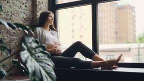 相当少妇妊妇爱抚她的腹部坐窗口基石,然后享受从窗口的看法 股票视频