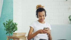相当少妇学生发短信给在网上聊天和听到音乐的朋友通过基于沙发的耳机 股票录像