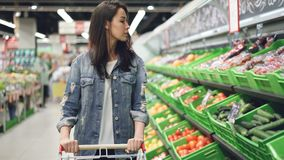 相当少妇沿推挤购物台车和看有机食品与的水果和蔬菜行走 股票录像