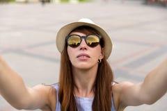 相当少妇游人采取在城市广场的selfie画象,里加,拉脱维亚 美丽的女学生拍旅行的照片 免版税库存照片