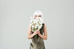 相当少妇用花花束盖了她的面孔 库存照片