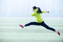 相当少妇跳跃的佩带的绿色运动服。 免版税库存照片