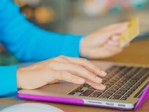相当少妇递拿着信用卡和使用片剂、智能手机和便携式计算机 免版税库存照片