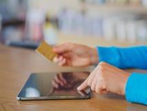 相当少妇递拿着信用卡和使用片剂、智能手机和便携式计算机 免版税库存图片