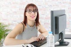 相当工作在个人计算机的年轻女商人在办公室 库存照片