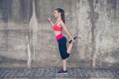 相当年轻亭亭玉立的教练员通过做exerci舒展她的腿 库存照片