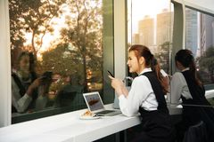 相当年轻企业亚裔妇女工作坐在大厦的一台膝上型计算机 库存图片