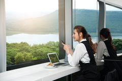 相当年轻企业亚裔妇女工作坐在大厦的一台膝上型计算机 免版税库存图片