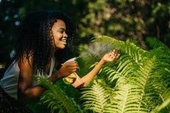 相当年轻卷曲非洲女孩的画象有可爱的微笑、绿色唇膏和保重蕨的眼影的 免版税图库摄影