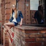 相当年轻坐的女孩室外时尚生活方式画象,佩带在行家赃物难看的东西样式都市背景中 库存图片