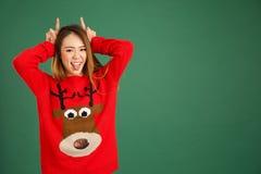 相当年轻新加坡女孩佩带的圣诞节套头衫和做 库存照片