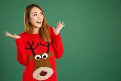 相当年轻新加坡女孩佩带的圣诞节套头衫和smili 免版税库存图片