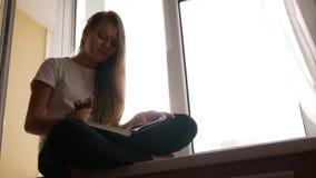 相当年轻白肤金发的女孩通过书吃蛋糕和翻转坐窗台 股票录像
