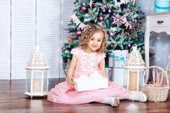 相当微笑与礼物的小白肤金发的女孩在圣诞树附近 圣诞节的概念 库存照片