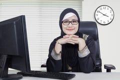 相当微笑在办公室的阿拉伯妇女 免版税库存照片