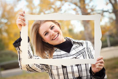 相当微笑在有画框的公园的少妇 库存图片