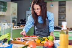 相当微笑对照相机的少妇,当装饰一个蛋糕用坐在大厨房里时的切的草莓 免版税库存照片