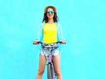 相当微笑的少妇骑在五颜六色的蓝色的一辆自行车 免版税库存图片