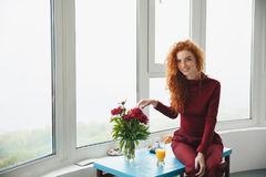 相当快乐的年轻红头发人夫人坐桌 免版税图库摄影