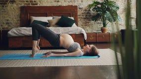 相当怀孕的夫人在穿舒适的产科运动服的卧室做着在瑜伽席子的体育锻炼 健康 股票录像